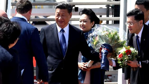 China's President Xi Jinping (C-L) and his wife Peng Liyuan (C-R) are greeted as they arrive at the airport in Hamburg, northern Germany on July 6, 2017, to attend the G20 meeting. (Patrik Stollarz / AFP)