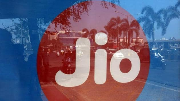 Commuters are reflected on an advertisement of Reliance Industries' Jio telecoms unit, at a bus stop in Mumbai.(Reuters)