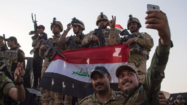 """Members of the Iraqi forces celebrate in the Old City of Mosul after the government's announcement of the """"liberation"""" of the embattled city from Islamic State on Monday.(AFP Photo)"""