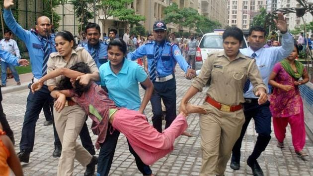 Police in action against local villagers who gathered at a housing society to protest after a domestic help was allegedly beaten by her employers on suspicion of theft, in Noida on Wednesday(PTI)