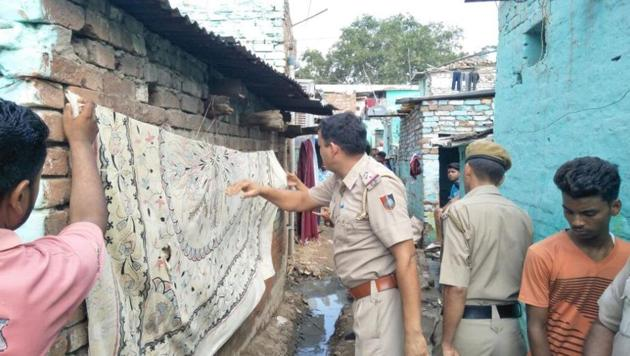 Police officials covering the defacement at Colony number 4 in Industarial Area, Chandigarh, on Saturday.(HT Photo)