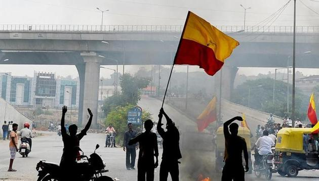A file phot of activists in Bengaluru waving the Karnataka flag as they block traffic on a connecting road during a statewide strike over water shortage.(AFP)