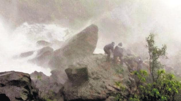 Rescuers try to pull Ramesh Mane out of the 150-ft gorge he fell into while on a trip with his friends on Sunday.(HT PHOTO)