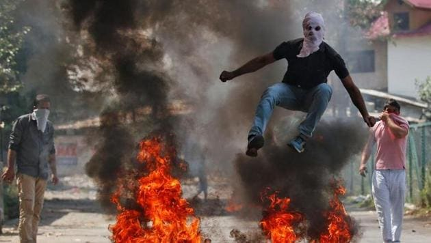 A man jumps over burning debris during protests in Srinagar. The Valley has been shaken by violent protests since July last year, leading to dozens of civilian deaths.(Reuters File Photo)