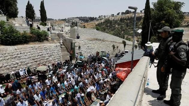 Israeli border police officers stand guard as Palestinians pray at Lions' Gate, the entrance to Jerusalem's Old City, in protest over Israel's new security measures at the compound housing al-Aqsa mosque, known to Muslims as Noble Sanctuary and to Jews as Temple Mount July 20.(Reuters Photo)