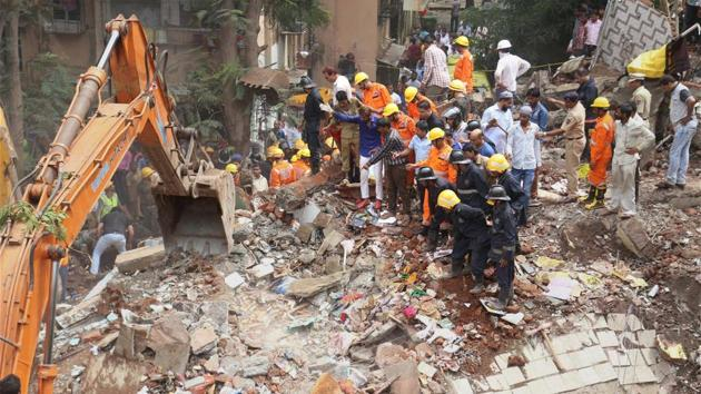 Fire brigade and rescue personnel at work at the site of a building collapse in Mumbai on Tuesday.(PTI)