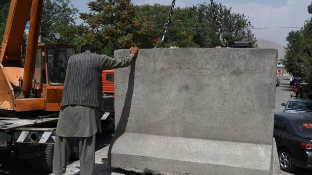 An Afghan government worker removes blast walls in Kabul. The blast walls that cut through Kabul like ramparts are being pulled down, part of a counter-intuitive makeover by local officials who argue the move will give the city's war-weary residents a psychological boost.(AFP Photo)