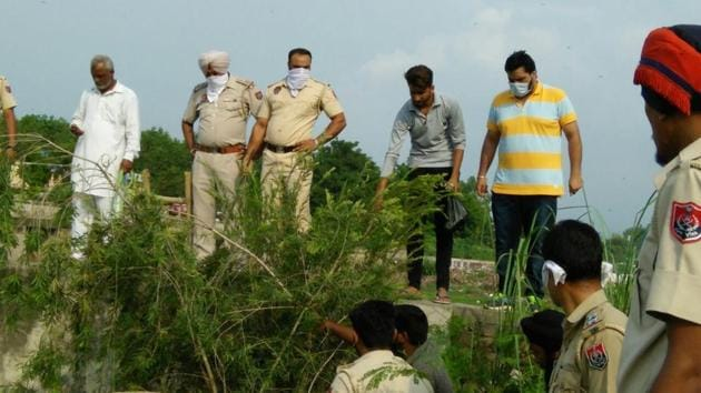 Police officials and villagers during the search operation at Kangna village in SBS Nagar on Wednesday.(HT Photo)