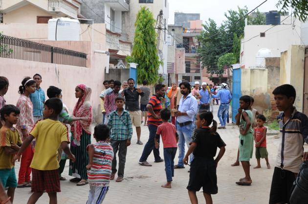 Neighbours of a woman in Devi Lal colony who claimed her hair was mysteriously chopped.(Parveen Kumar/HT PHOTO)