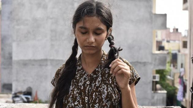 A girl shows her chopped braid in Mayapuri. The family claims that someone cut the hair of four women when they were asleep. Similar reports were received from Rohini and Pandav Nagar too.(Burhaan Kinu/HT PHOTO)