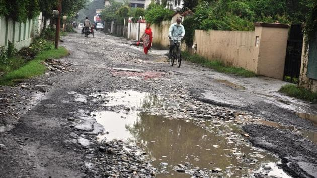 A view of pothole filled Canal Road in Dehradun.(Vinay Santosh Kumar/HT PHOTO)