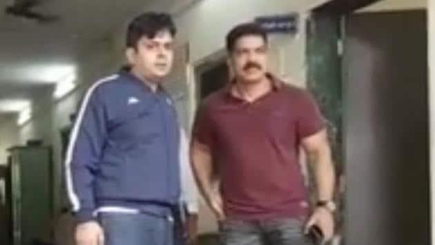 The accused stalker Niteshkumar Sharma (left) with police officer Daya Nayak at Amboli police station in Mumbai.(ANI Photo)