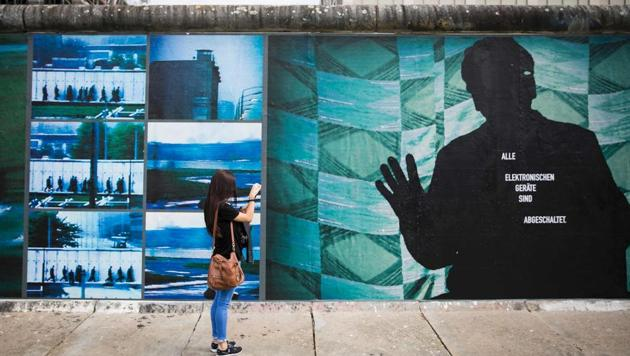 """A woman takes pictures of the installation """"Beyond The Wall"""" by German artist Stefan Roloff that is mounted on remnants of the former Berlin Wall.(AFP Photo)"""