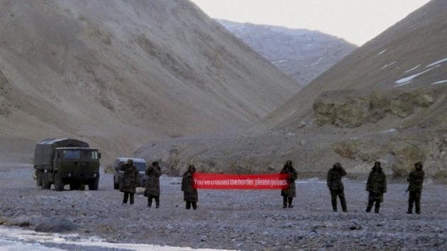 """In this 2013 photo, Chinese troops hold a banner which reads """"You've crossed the border, please go back"""" in Ladakh.(AP File Photo)"""