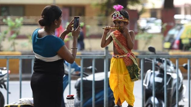 A woman takes a picture of her son dressed as Lord Krishna in Mumbai on Friday.(Satyabrata Tripathy/ HT Photo)