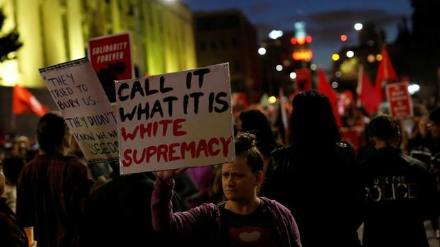 """A demonstrator holds signs during a rally in response to the Charlottesville, Virginia car attack on counter-protesters after the """"Unite the Right"""" rally organized by white nationalists, in Oakland, California, US.(Reuters Photo)"""