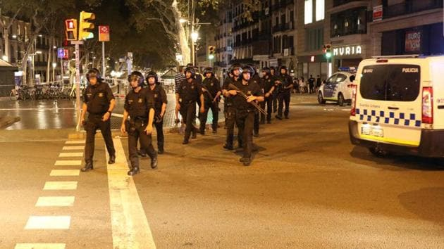 Armed officers leave the area where a van crashed into pedestrians at Las Ramblas in Barcelona, Spain, on Friday.(Reuters)