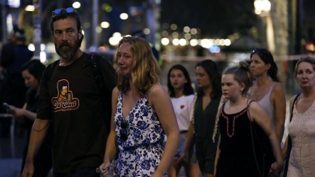 A woman cries as she and others are escorted by Spanish policemen outside a cordoned off area after a van ploughed into the crowd, killing 13 persons and injuring over 100 on the Rambla in Barcelona on August 17, 2017.(AFP Photo)