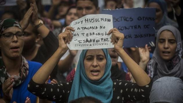 """A woman holds a banner reading in Spanish: """"I am Muslim and Catalan, not a terrorist. Islam is Peace"""", during a protest by the Muslim community to condemn the vehicle attacks, in Barcelona, Spain, on Saturday, Aug. 19, 2017.(AP)"""