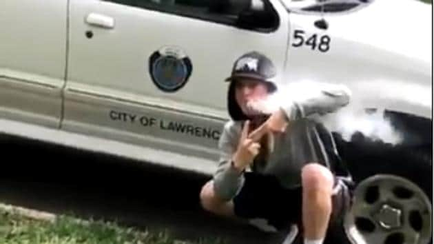 The Lawrence Police Department in the US re-tweeted a boy's video in which he spots an official car of the City of Lawrence and poses next to it while blowing smoke.(Screen grab/Twitter)
