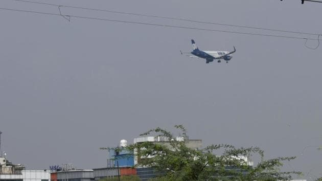 A plane flying low over Dwarka, following its descent before landing at Delhi's Indira Gandhi International Airport. Pilot of an international flight on Sunday had reported seeing a drone-like object near the airport, triggering a security scare.(Vipin Kumar/HT Photo)
