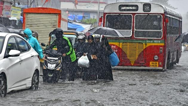 People walk through a flooded road at Andheri in Mumbai on Tuesday, August 29, 2017. (HT Photo / Shashi S Kashyap)