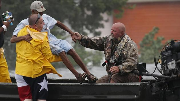 Rescuers help a man from the flooding of Hurricane Harvey on August 30, 2017 in Port Arthur, Texas.(AFP Photo)
