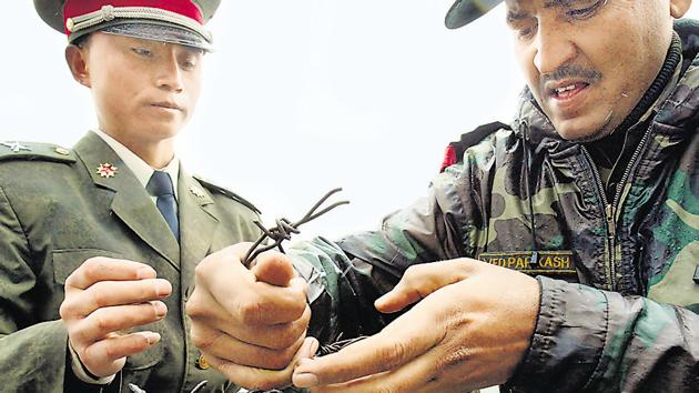 File photo from July 2006 shows a Chinese soldier (left) and an Indian soldier placing a barbed wire fence following a meeting of military representatives at Nathu La border crossing in India's northeastern Sikkim state.(AFP)