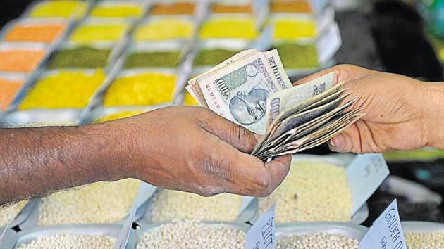 A customer hands over cash to a merchant at a wholesale trading shop in Bengaluru. Indian shares ended higher on August 31, pulling back from losses earlier in the session, as investors awaited GDP data for the April-June quarter.(AFP File Photo)