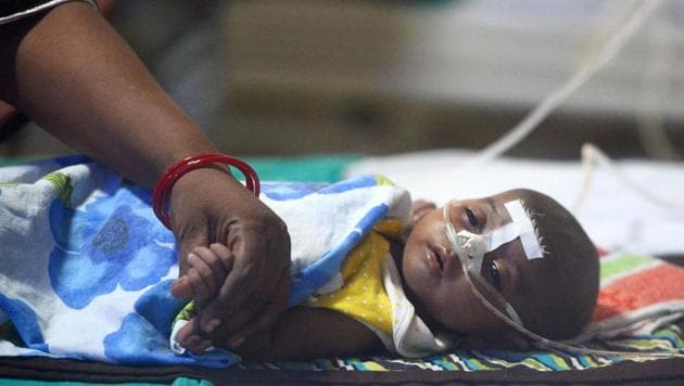 A woman holding her child's hand at the encephalitis ward of the Baba Raghav Das Hospital in Gorakhpur on August 14.(AFP File Photo)