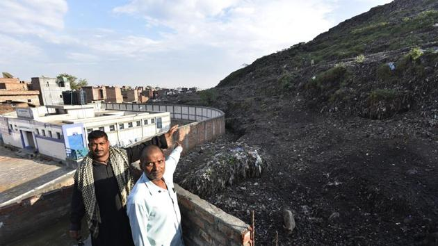 Residents of Bhalswa pointing out at the landfill near their houses.(Raj K Raj/HT PHOTO)