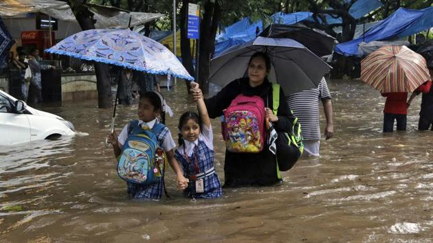 Schoolchildren walk through a waterlogged street in Mumbai. Unicef said almost 16 million children and their families are in urgent need of life-saving support.(AP)