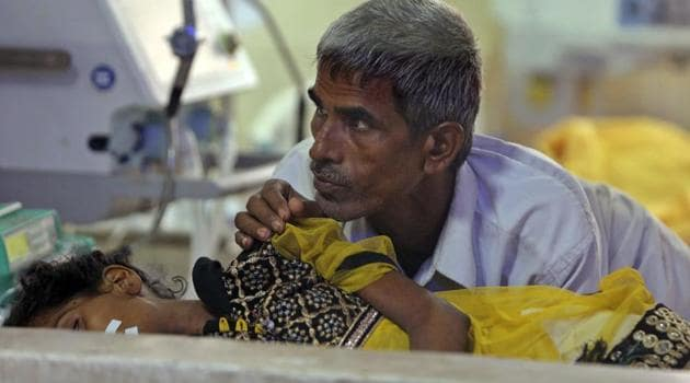 A relative attends to a child receiving treatment at the state-run Baba Raghav Das Medical College Hospital in Gorakhpur where children died due to a lack of oxygen supply.(AP File Photo)