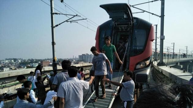 Passengers being taken out of the emergency exit after a Lucknow Metro train developed a snag on Wednesday. (HT photo)