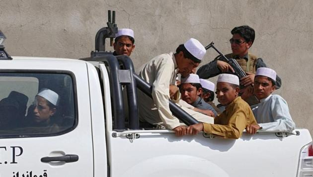 In this photograph taken on July 15, 2017, Afghan children, who were released from being held by kidnapping gangs, are brought to the police headquarters in Ghazni province. The rescue this summer of dozens of Afghan youths destined for Pakistan religious schools to be trained as Taliban fighters has bolstered claims that insurgents are increasingly recruiting children to reinforce their ranks.(AFP)