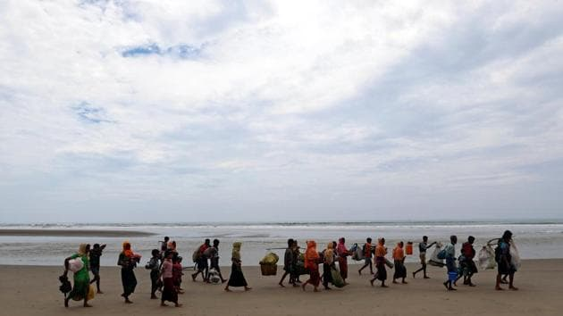 Rohingya refugees walk on the shore with their belongings after crossing the Bangladesh-Myanmar border by boat through the Bay of Bengal in Teknaf, Bangladesh, September 7, 2017.(REUTERS Photo)