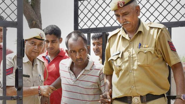 Bus conductor Ashok Kumar being escorted by police.(Sanjeev Verma/HT Photo)