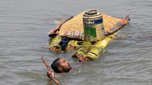 A villager carries grains on a banana raft as he shifts from a flooded village in Araria district of Bihar.(PTI File Photo)