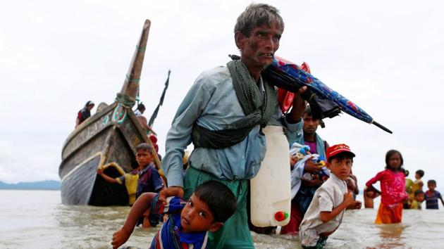 A Rohingya refugee man pulls a child as they walk to the shore after crossing the Bangladesh-Myanmar border by boat through the Bay of Bengal in Shah Porir Dwip, Bangladesh, September 10.(Reuters Photo)