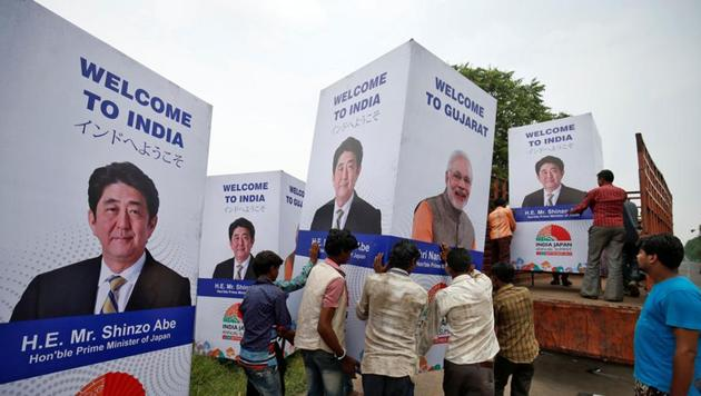 Workers carry hoardings featuring Prime Minister Narendra Modi and his Japanese counterpart, Shinzo Abe, in Ahmedabad on Monday. Abe arrives in the Gujarat capital on Wednesday.(REUTERS)