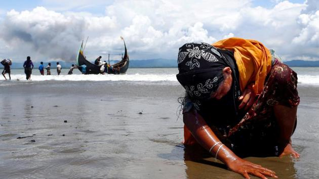 An exhausted Rohingya refugee woman touches the shore after crossing the Bangladesh-Myanmar border by boat through the Bay of Bengal, in Shah Porir Dwip, Bangladesh, on Monday.(Reuters Photo)