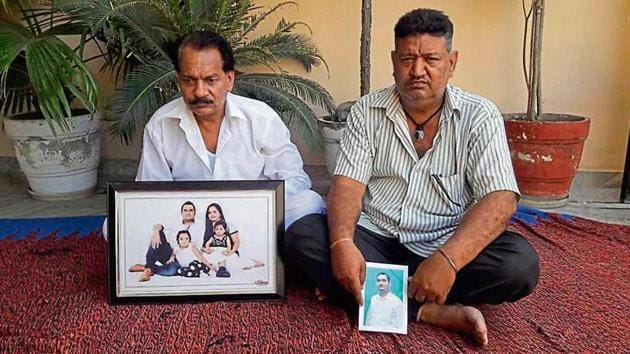 Family members holding the pictures of deceased Lalit and his missing uncle Talwinder Singh in SBS Nagar on Friday.(HT Photo)