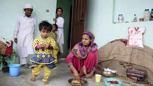 A Rohingya refugee feeds her daughter in a building on the outskirts of Srinagar on September 14, 2017. Eighteen families of Rohingya refugees from Myanmar have been living in Srinagar for the past six months, some of the almost 6000 Rohingya refugees who are living in 18 refugee camps in India since 2012 Rakhine state riots.(AFP File Photo)