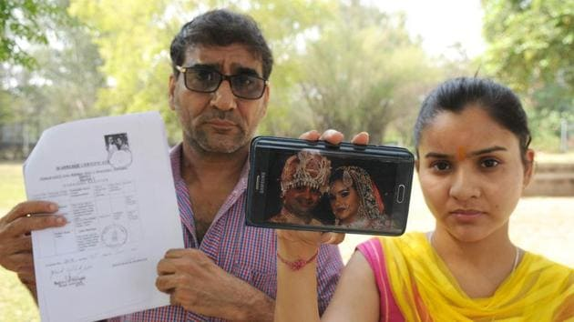Sarita Dharna with her father Jai Gopal from Jalandhar during the National Seminar on NRI marriage in Chandigarh on April 20. Savita was abandoned by her NRI husband.(HT)