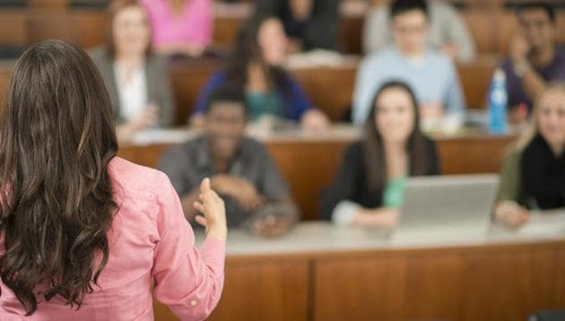 A multi-ethnic group of college age students are sitting in a row in a lecture hall and are listening to their professor.(Getty Images)