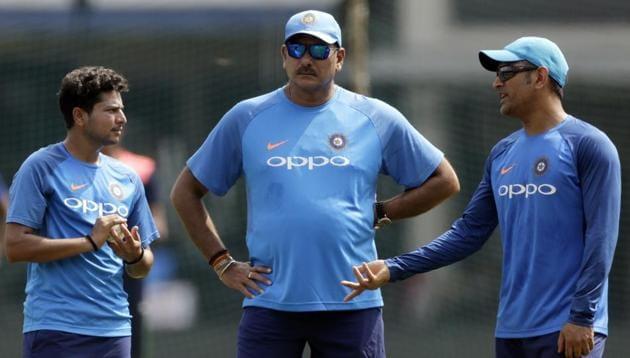 <p>Kuldeep Yadav, Ravi Shastri and MS Dhoni strategise ahead of third India vs Australia ODI in Indore.</p> (AP)