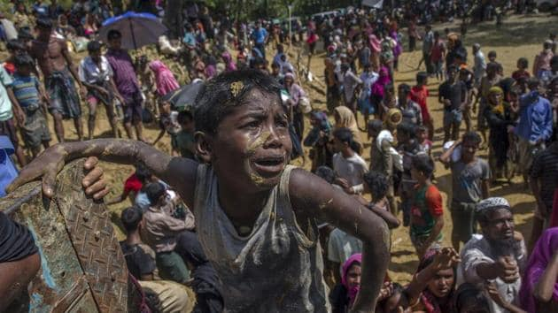 A Rohingya Muslim boy, who crossed over from Myanmar into Bangladesh, pleads with aid workers to give him a bag of rice near Balukhali refugee camp, Bangladesh, September 21(AP)