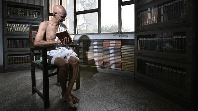Mahesh Chaturvedi sits in a public library in central Delhi that faces a life-size mural of his idol and inspiration Mahatma Gandhi. The 68-year-old Chaturvedi calls himself a modern-day Gandhi -- complete with round glasses, a crisp white dhoti and a message to wipe out poverty.(Arun Sharma / HT Photo)