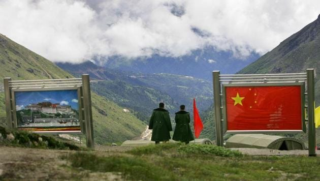 Chinese army officers stand on the Chinese side of the international border at Nathula Pass in Sikkim in July 2006.(AP File Photo)