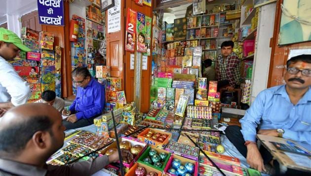 People buy firecrackers near Jama Masjid in old Delhi on Monday. The Supreme Court has banned the sale of firecrackers in Delhi till November 1.(PTI)